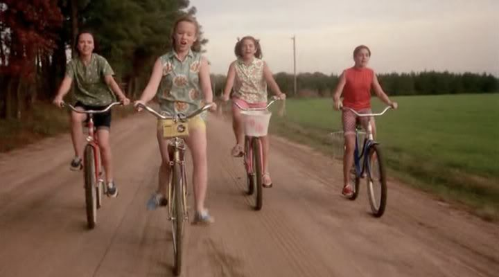 Four adolescent girls ride bicycles on a dirt road in a nostalgic 1950s setting