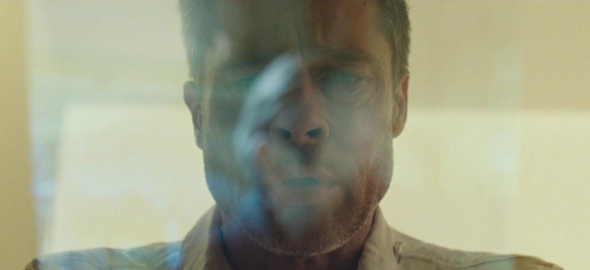 Brad Pitt as Roy McBride gazes down towards something below the frame. His expression is concerned, though his face is obscured by reflections.